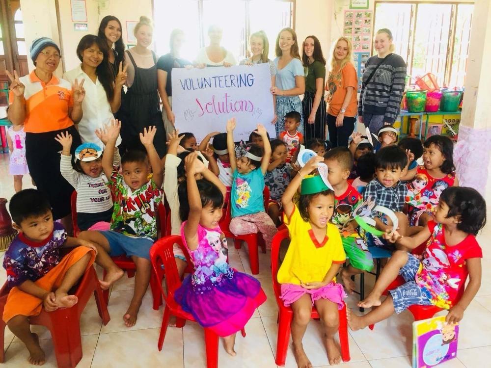 Voluntários brincando com crianças durante seu projeto na Tailândia>