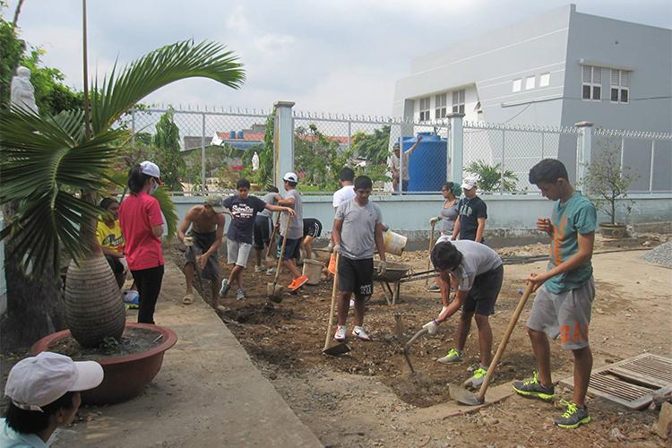 Estudiantes trabajando en un proyecto de construcción en Vietnam.>