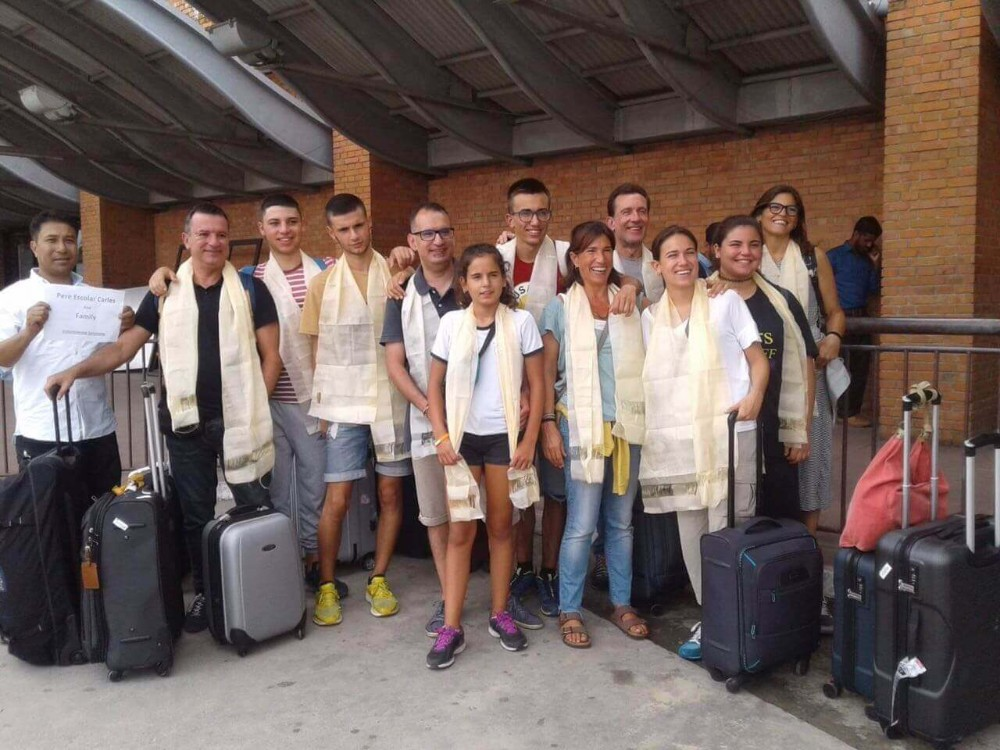 Volunteers receive a traditional welcome at at the airport in Nepal >