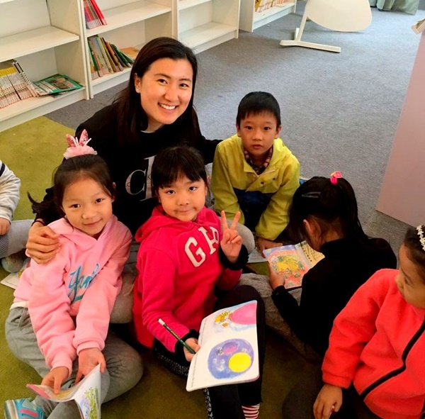 Christina Li with children in school